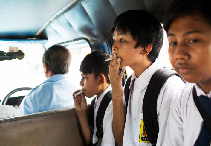 Children smoke on a public bus home from school on February 12, 2014 in Jakarta, Indonesia. Although there are smoking regulations in public places there is a lack of enforcement.